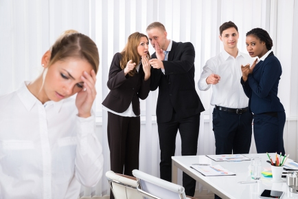 Businesspeople Gossiping Behind Stressed Female Colleague In Office