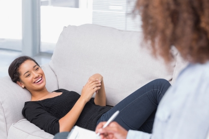 Woman lying on therapists couch looking happy as therapist is wr