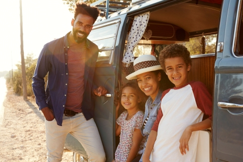 Young family make a stop on a road trip in their camper van